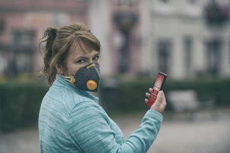 Frau, die eine echte Anti-Pollution-, Anti-Smog- und Viren-Gesichtsmaske trägt und die aktuelle Luftverschmutzung mit der Smartphone-App überprüft Standard-Bild