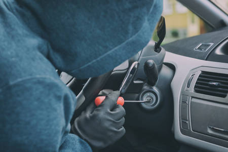 Hooded thief sits in the car and tries to break the ignition switch with a screwdriver