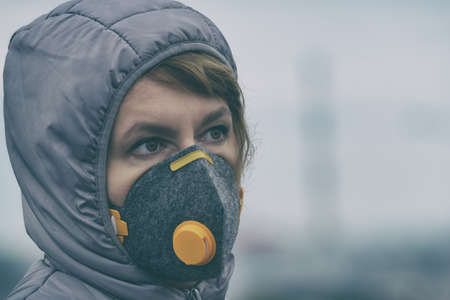 Woman wearing a real anti-pollution, anti-smog and viruses face mask; dense smog in air. Фото со стока - 132391834