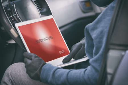 Hooded thief tries to break the car's security systems with laptop. Hacking modern car concept Фото со стока - 132457199