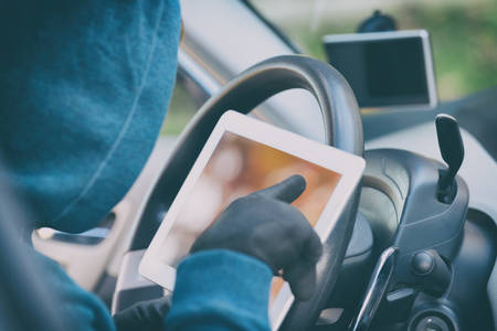 Hooded thief tries to break the car's security systems with tablet. Hacking modern car concept Фото со стока - 132457608