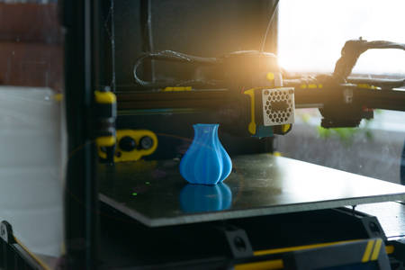 Modern 3d printer with printed three dimentional model of vase.