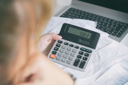 Woman uses a calculator to sum up expenses and holds her head worrying about the amount of money spent