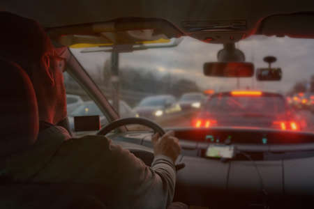 Driving a car in the city at night in traffic jams. the concept of a difficult return home Фото со стока