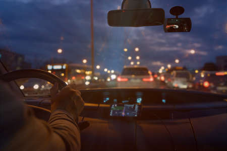 Driving a car in the city at night in traffic jams. the concept of a difficult return home 免版税图像