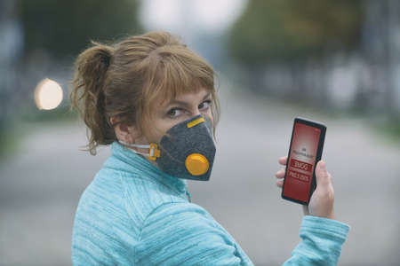 Woman wearing a real anti-pollution, anti-smog and viruses face mask and checking current air pollution with smart phone app Фото со стока - 133663869