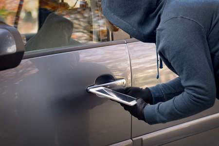 Hooded thief tries to break the cars security systems with tablet. Hacking modern car concept Фото со стока