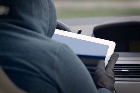Hooded thief tries to break the car's security systems with tablet. Hacking modern car concept Фото со стока - 133663932