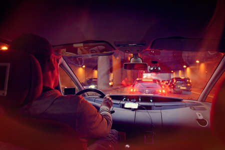Driving a car in the city at night in traffic jams. A concept of a difficult return home Фото со стока