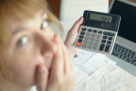 Woman uses a calculator to sum up expenses and holds her head worrying about the amount of money spent Фото со стока - 133663939