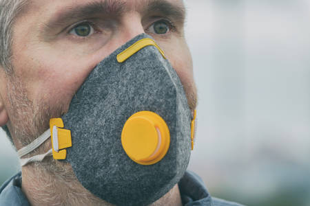 man wearing a real anti-pollution, anti-smog and viruses face mask; dense smog in air Фото со стока - 133663999
