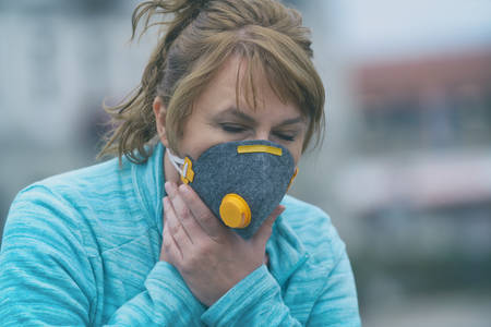 Woman wearing a real anti-pollution, anti-smog and viruses face mask; dense smog in air. Фото со стока