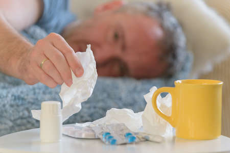 Man suffering from flu or cold lies sadly covered with a blanket on his bed. Drugs, medicines, cup and tissues in foreground Фото со стока