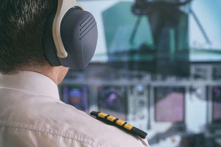 Close up of captains epaulettes and headphones in the cockipt of commercial airplane