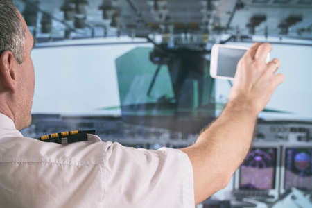 Airline pilot wearing uniform with epauletes taking pictures with smart phone in airplane cockpit Фото со стока