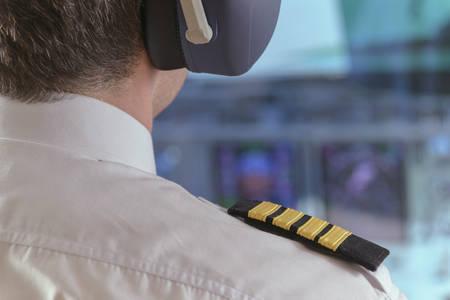 Nahaufnahme der Schulterklappen und Kopfhörer des Kapitäns im Cockpit des Verkehrsflugzeugs
