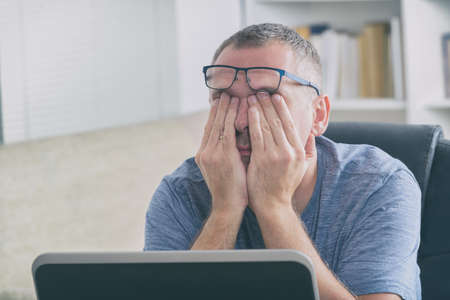 Tired freelancer man rubbing his eye while working with laptop