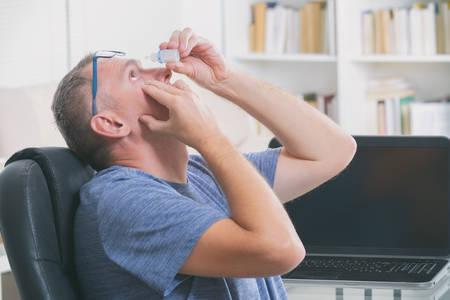 Man applying eye drops after a long sitting at computer Фото со стока