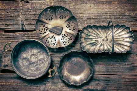 Old used silver and steel dishware on wooden board