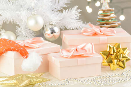 Christmas gifts under the white Christmas tree with red cap and gold ribbon Фото со стока