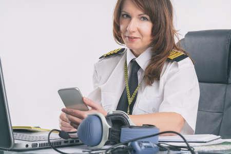 Beautiful woman pilot wearing uniform with epaulettes doing preflight briefing