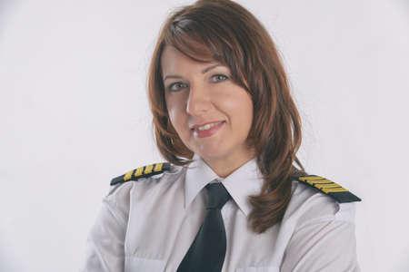 Beautiful woman pilot wearing uniform with epauletes, standing isolated on white background. Фото со стока