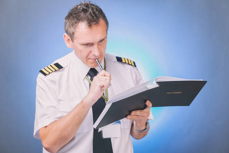 Airline pilot wearing shirt with epaulets and tie filling in filling in and checking papers logbook and checking papers and weather forecast Фото со стока