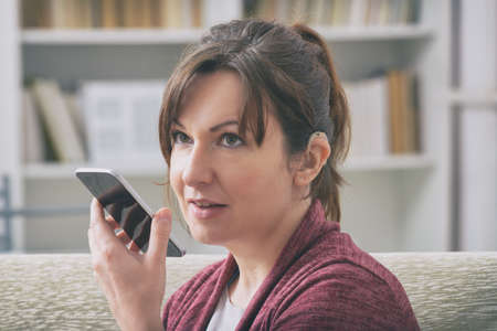 Deaf woman wearing hearing aid and using smartphone
