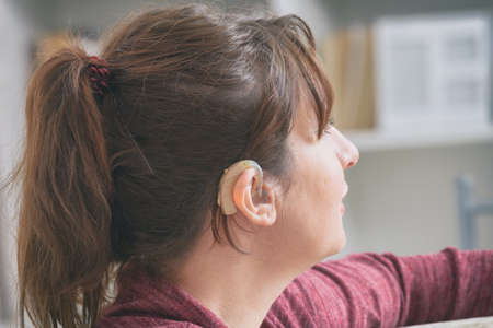 Smiling deaf woman wearing hearing aid