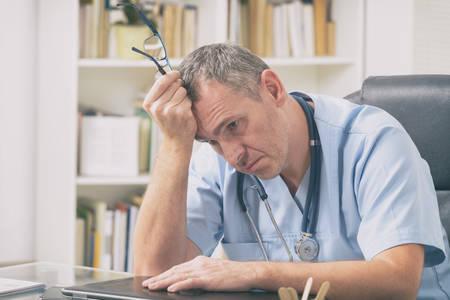 Überarbeiteter Arzt, der in seinem Büro sitzt Standard-Bild