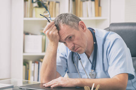 Overworked doctor sitting in his office Stock Photo
