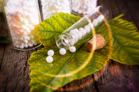 Homeopathic lactose sugar globules on leaf with glass bottle Foto de archivo