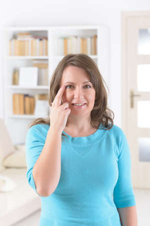 Woman doing EFT on the side of eye point. Emotional Freedom Techniques, tapping, a form of counseling intervention that draws on various theories of alternative medicine.