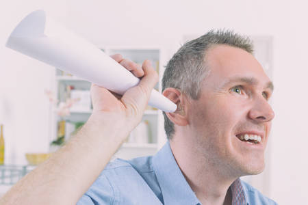 Man wearing deaf aid in ear attempting to hear something Stock Photo
