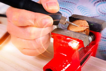 Woman using a high speed rotary multi tool to engrave ornament on slice of wood. Tool could be used as grinder