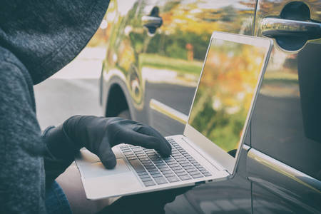 Hooded thief tries to break the cars security systems with laptop. Hacking modern car concept