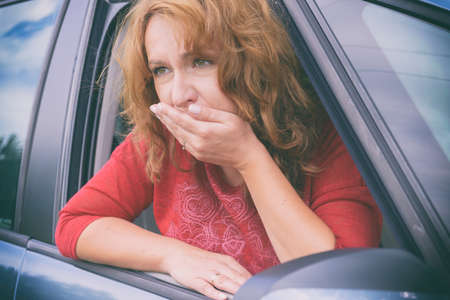 Woman suffering from motion sickness in a car