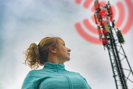 The woman is standing near the BTS. Harmful radiation from cellular 5G network transmitters concept