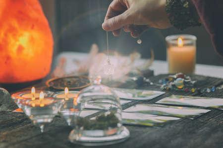 Fortune teller holding a pendulum over tarot cards