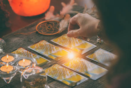 Fortune teller holding a pendulum over tarot cards Stockfoto - 149715972
