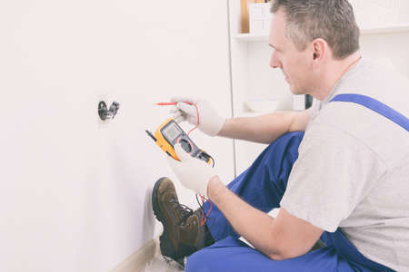 Electrician checking socket voltage with digital multimeter