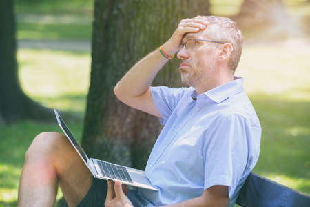 Man suffers from heat while working with laptop in the park and wiping his forehead Stock fotó