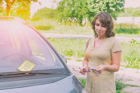 Unhappy woman showing parking ticket. Focus on ticet