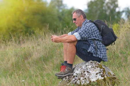 Man backpacker sitting on a rock with smartphone