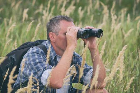 Close up of a man looking through binoculars, outdoors.