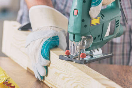 Man cutting a piece of wood using a jigsaw