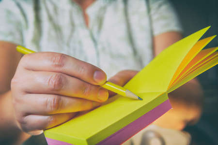 Woman taking notes with yellow pencil. Close up on the notepad.