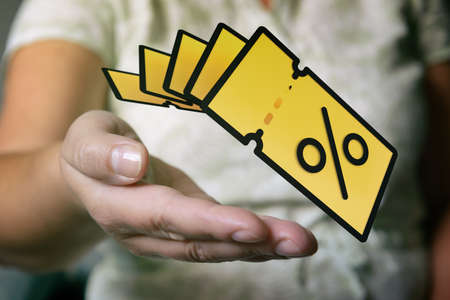 Hand with yellow promo code coupons. Sale or discount conceptual photo.