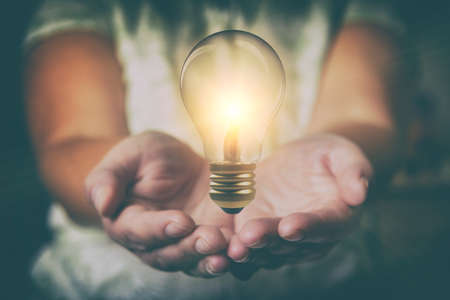 Lightbulb floating over wonan's hands. Could be illustarion of brainstorming or new ideas comming.