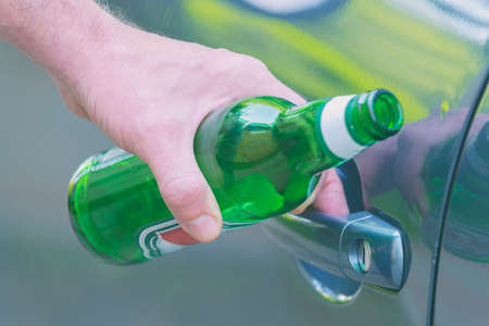 Man opening his car while holding a bottle of beer. Don't drink and drive concept Imagens